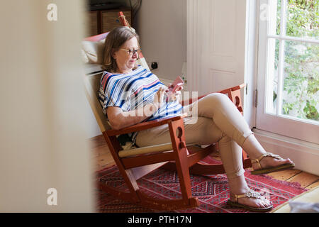 Senior woman texting with smart phone in rocking chair - Stock Image