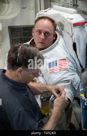 Commercial Crew Program astronaut Mike Fincke, is assisted with his spacesuit by Boeing astronaut Chris Ferguson during Quest Airlock simulation for ISS EVA training in preparation for future spacewalks while onboard the International Space Station at the Johnson Space Center February 6, 2019 in Houston, Texas. - Stock Image