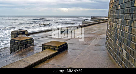Waves breaking against the sea defences in Scarborough's South Bay. - Stock Image
