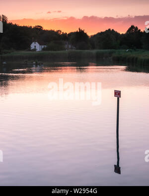 a calm lake at sunset with a no fishing sign reflecting on the water - Stock Image