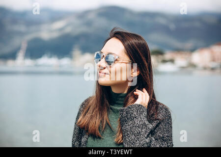 Portrait of a young beautiful girl in sunglasses on the background of the sea. - Stock Image