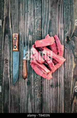 Uncooked raw boneless beef ribs with vintage meat fork and butcher's knife over top a rustic wood table / background. Image shot from overhead view. - Stock Image