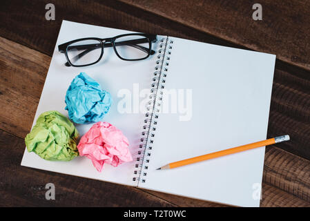 Eyeglasses, crumpled paper and blank spiral notebook with copy space on a wooden table. Concept of school, writing, sketching and workspace. - Stock Image