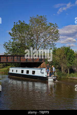 """A """"Dream Come True"""" for some one, a canal narrow boat passes under a railway  bridge on the Trent and Mersey canal on a spring day in Cheshire. - Stock Image"""
