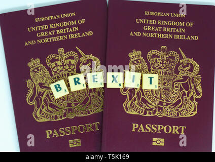 2 European Union United Kingdom of Great Britain passports with Brexit written with Scrabble tiles - Stock Image