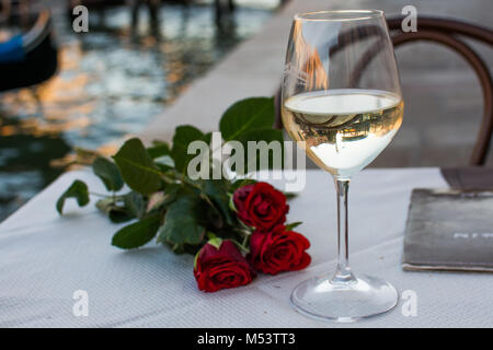 beautiful roses and red wine in front of the amazing Grande canal in Venice, Italy - Stock Image