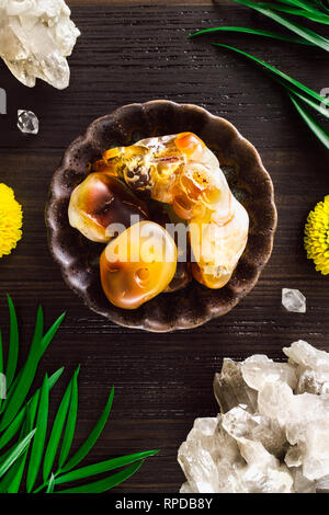 Fire Agate with Smoky Quartz and Mums on Dark Wood - Stock Image