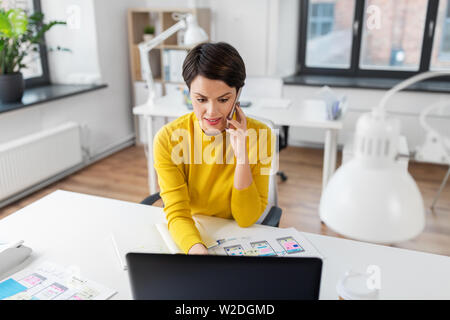 ui designer calling on smartphone at office - Stock Image