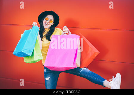 Happy fashion Asian woman doing shopping in mall center - Young Chinese girl having fun buying new clothes and celebrating against a red background - Stock Image