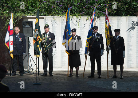 Portsmouth, UK. 15th Aug, 2015. Flag bearers stand to attention during the start of the VJ 70 memorial in Portsmouth. - Stock Image