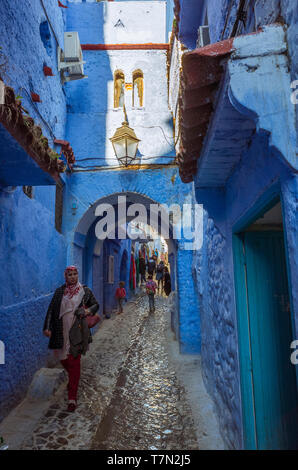 Chefchaouen, Morocco : A Moroccan woman walks under an arch in the blue-washed medina old town. - Stock Image