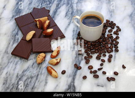 Things from Brazil, coffee, coffee beans, chocolate, brazil nuts on a marble slab. - Stock Image