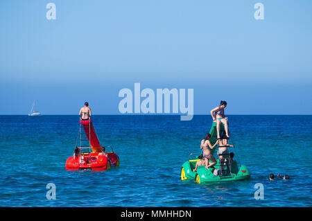 Young women riding colourful pedalos in the Mediterranean sea on a warm summer's day in Cala San Vicente, Mallorca, Spain. - Stock Image