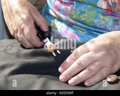 Hand with scissors cut out button of dresses - Stock Image