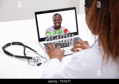 Close-up Of A Happy Doctor Video Conferencing With Male Colleague On Computer In Clinic - Stock Image
