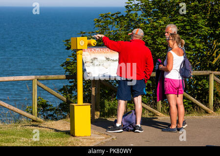 UK, England, Yorkshire, Filey, Crescent Gardens, visitors at coin operated telescope over Filey Bay at John Paul Jones sea battle information board - Stock Image