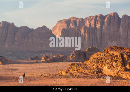 Bedouin man walking across desert, Wadi Rum, Jordan - Stock Image