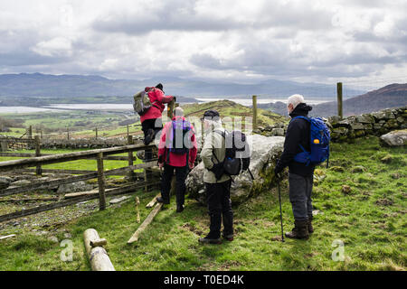 Ramblers walking on a country walk climbing over a stile in countryside on edge of Snowdonia. Tremadog, Gwynedd, Wales, UK, Britain - Stock Image