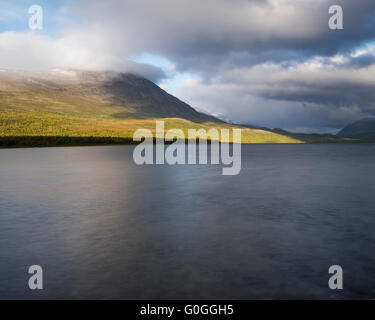 Mountains rise above lake Teusjaure, near Teusajaure hut, Kungsleden trail, Lapland, Sweden - Stock Image