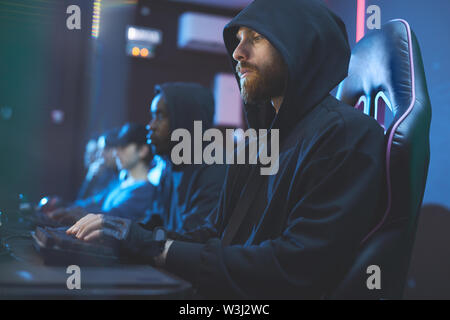 Serious geek guy with beard wearing black hoodie sitting in comfortable chair and searching for information on internet while using computer - Stock Image