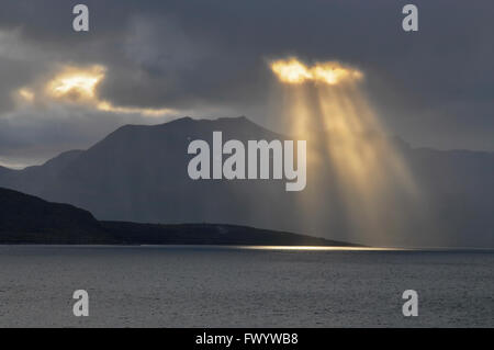Sun rays are breaking through thick rain clouds at Kvæfjord on island Hinnøya in northern Norway - Stock Image