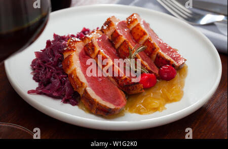 Fried duck breast  Magre served  with boiled cabbage and caramelized onions at plate - Stock Image