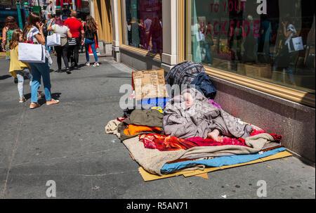 Homeless sleeping on the sidewalk in Manhattan New York - Stock Image