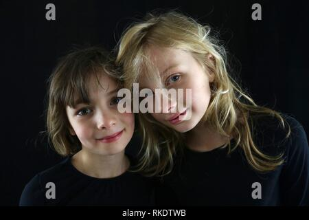 Two young girls putting their heads together for a portrait against a black background - Stock Image