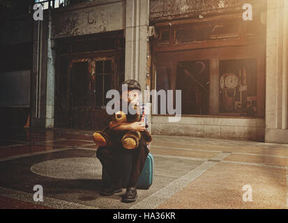 A scared young boy is sitting on a travel suitcase in an old building holding a teddy bear for a loneliness or safety - Stock Image
