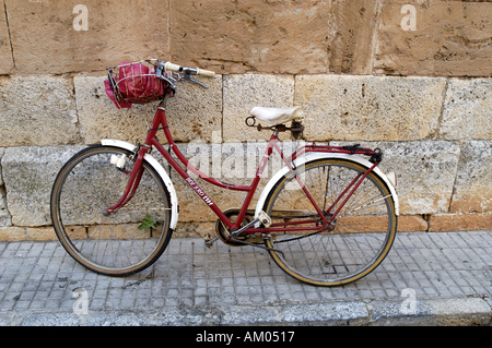 A red bike leaning against an old, brick wall. - Stock Image