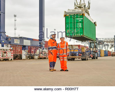 Dock workers by crane lowering cargo container onto truck - Stock Image