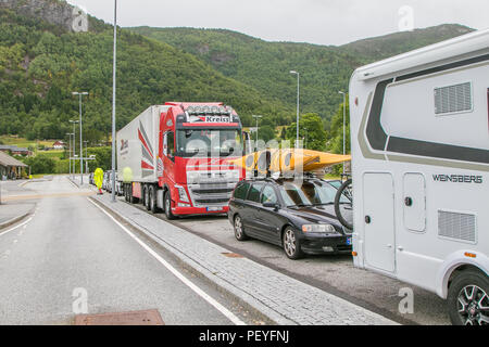 Oppedal, Norway, July 23, 2018: Cars and trucks stand in line to board a ferry boat that will bring them across a fjord. - Stock Image