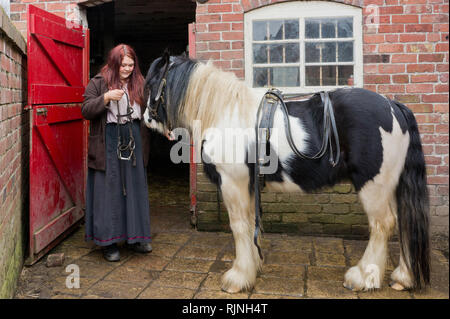Female groom, in period costume, harnessing a horse at Blists Hill Victorian Town, Shropshire, UK - Stock Image
