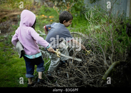 Boy aged six and sister five flush out imaginary foes from pile of tree cuttings with plastic toy swords - Stock Image