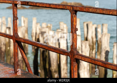 old rusty fence of Saint Malo with breakwater in the background - Stock Image
