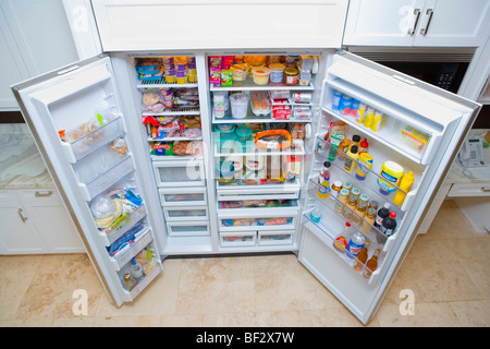 Refrigerator filled with assorted food items - Stock Image