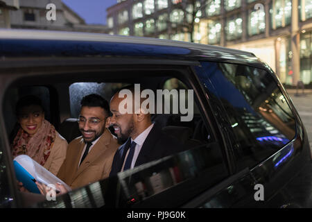 Business people reviewing paperwork in crowdsourced taxi at night - Stock Image