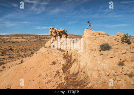 Full length of woman standing on rock formation against sky - Stock Image