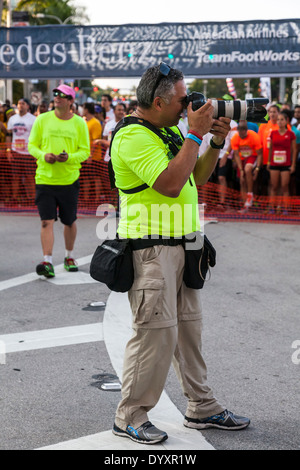 Professional photographer working the starting line of the 2014 Mercedes-Benz Corporate Run in Miami, Florida, USA. - Stock Image