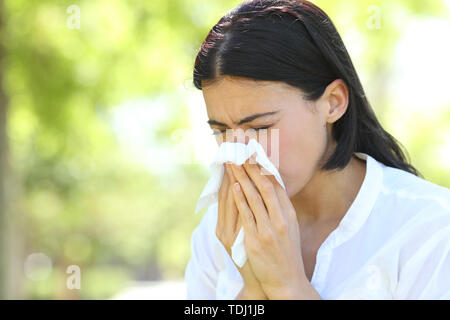 Ill woman sneezing covering mouth with a wipe standing in a park with a green background - Stock Image