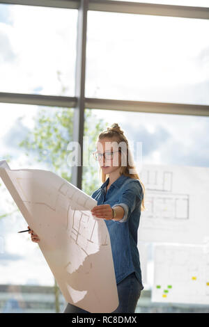 Woman contemplating plans by glass wall - Stock Image