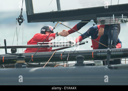 Portsmouth, UK. 25th July 2015. A handshake between crew as Ben Ainslie's Landcover BAR team secure second place - Stock Image