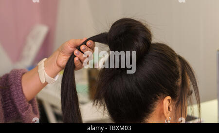 Professional hairdresser working with client in salon. Earlock hair in hairstylist's hand Master class to create upper bun hairstyle. Tutorial, advanc - Stock Image