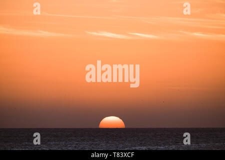 Classic tropical sunset or sunrise on the sea horizon with sun and water touching together - orange warm sky in background - travel destination paradi - Stock Image