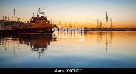 Torbay lifeboat moored in Brixham marina at sunset. - Stock Image