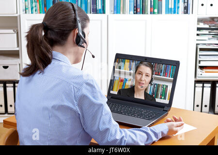 Rear view of a woman in a blue blouse with headset and laptop, having a live video call with her attorney, solicitor or lawyer, online legal advice - Stock Image
