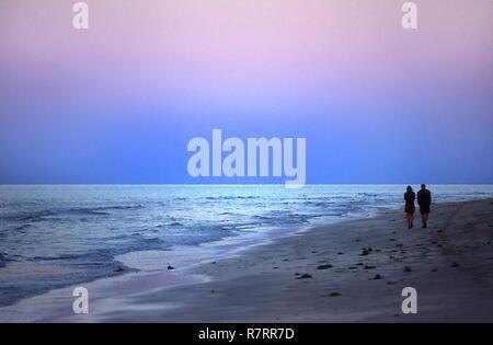 A couple walking on beach after sunset, Djerba, Tunisia - Stock Image