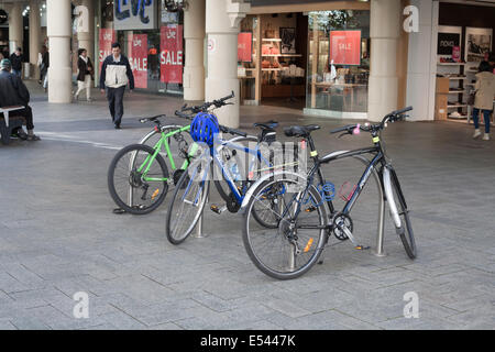 Bicycles parked and locked up at a bicycle or push bike stand. - Stock Image