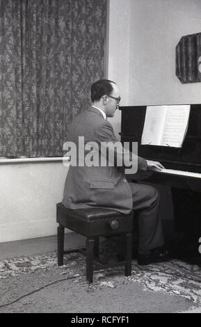 1950s, historical, a well-dressed man at home in his front room sitting on a stool playing a Rexall piano, England, UK. - Stock Image