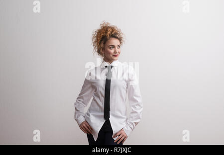 Young beautiful happy woman in studio standing against dark background, wearing white shirt and black tie. Copy space. - Stock Image